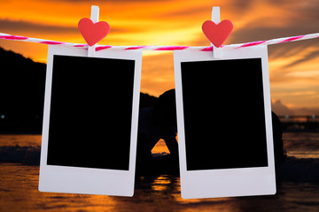 2 Blank instant photo and red clip paper heart hanging on the clothesline with beach sunset nature background..Designer concept.