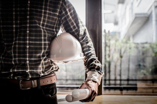 Smart Businessman holding construction helmet and blueprints in