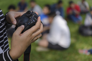 Asian woman holding a DSLR camera