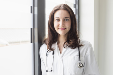 Portrait of a young female doctor standing in hospital
