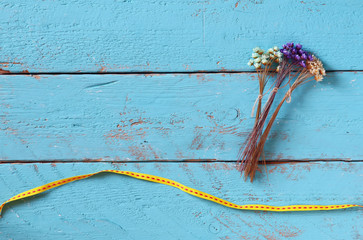 top view image of dried colorful flowers on old blue wooden background