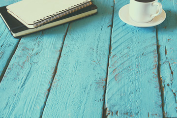 top view image of blank notebook next to cup of coffee. vintage filtered and toned