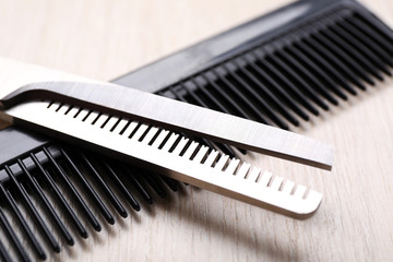 Barber set with scissors and comb on light wooden table, close up