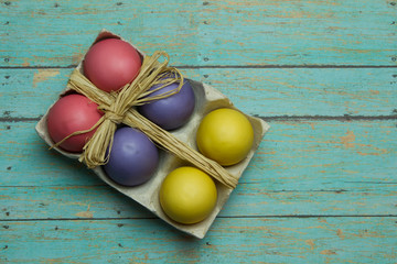 Colorful Easter Eggs with a Twine Bow on a Wood Background
