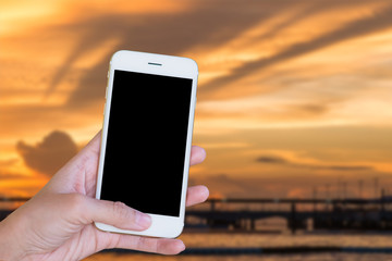 Hands woman are holding touch screen smart phone,tablet on blurred sunset sea nature background.