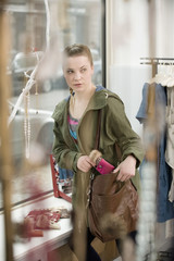 Germany, Bavaria, Young woman stealing something in fashion store