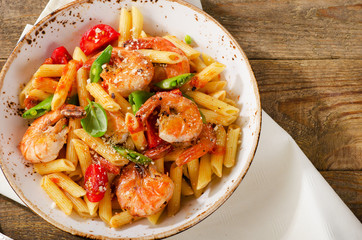 Penne pasta with shrimp, tomatoes and herbs on a wooden backgrou