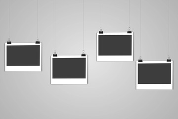4 blank photo frames hanging on line