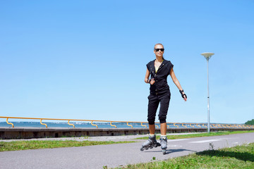 Young, beautiful, sporty and fit girl rollerblading on inline skates
