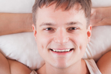 young man waking up in the morning in good mood. smiling