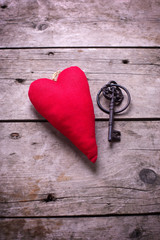 Decorative red   heart and vintage key on aged wooden background