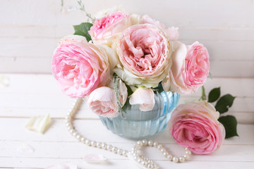 Background with sweet pink roses flowers  in blue vase on white