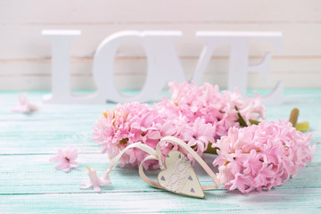Pink flowers, wooden word love and decorative heart   on turquoi