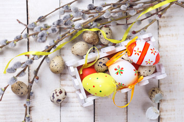 Colorful easter eggs in box, willow  branches on wooden backgrou