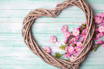 Decorative  heart and pink flowers  on turquoise wooden  backgro