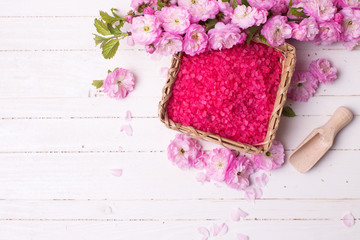 Spa or wellness setting. Pink sea salt in bowl  and pink flowers on white  wooden background. Selective focus is on salt..