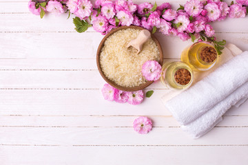 Sea salt in bowl, bottles with aroma oils, towels and pink flowe