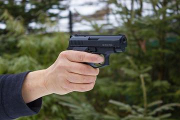 Frau schützt sich mit Pistole, bereit zur Selbstverteidigung.