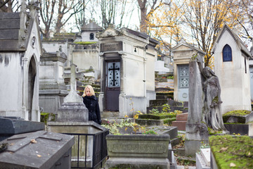 Solitary woman mourning by gravestone, remembering dead relatives in on Pere Lachaise cemetery in Paris, France.