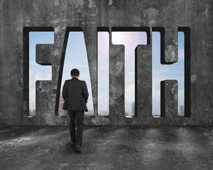 Faith word on concrete wall with man walking toward
