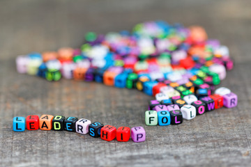 Leadership and follower words with dices on wooden table
