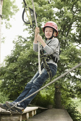 Germany, Bavaria, Boy climbing crag, smiling