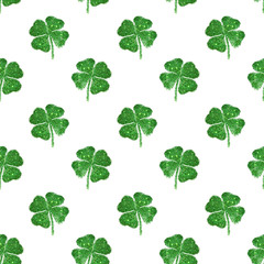 Seamless pattern of abstract four-leaf clovers of green glitter
