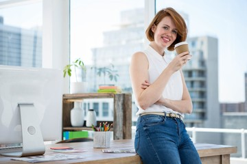 smiling hipster business woman drinking coffee in her office