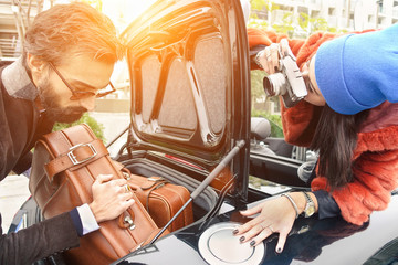 Hipster fashion couple having fun at loading leather suitcase
