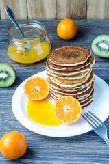 High tower of pancakes and mandarin sauce