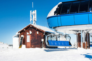 Ski resort image with  empty chair lift at high station, winter sunny day