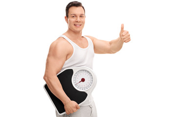 Guy holding a weight scale and giving thumb up