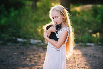 Baby girl holding hands a kitten in the light of sunset, pet, friend,