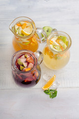 Healthy detox fruit infused flavored water. Summer refreshing homemade cocktail with fruits on white wooden table top view