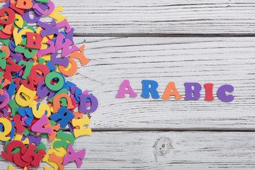 the colorful words arabic made with colorful letters over white wooden board