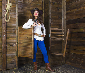 girl cowboy on wooden background wall in the hands of the gun