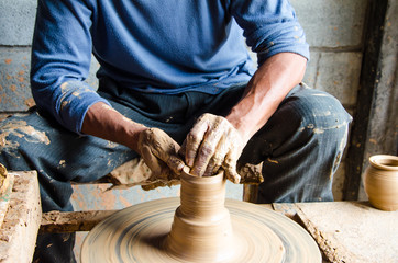 Hands of making clay pot on the pottery wheel ,select focus, close-up.