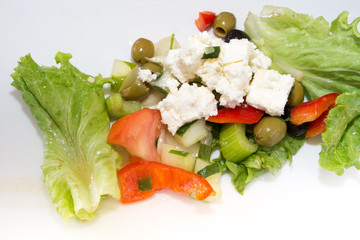 Greek vegetable salad with feta cheese on a white plate