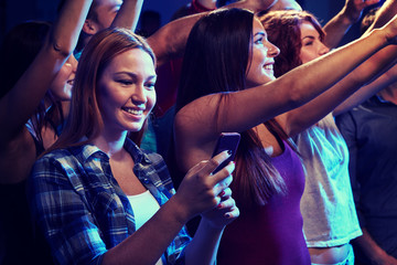 woman with smartphone texting message at concert