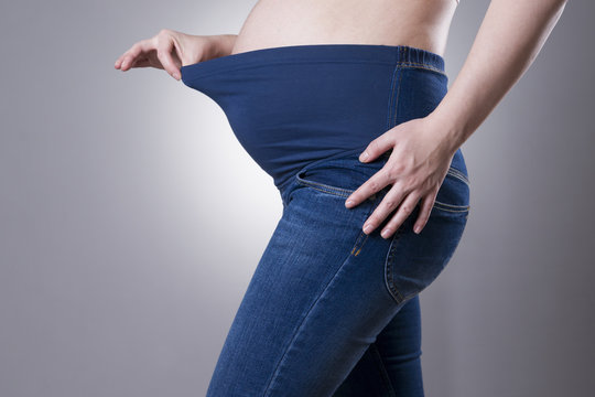 Pregnant woman in blue jeans for pregnant women on gray background