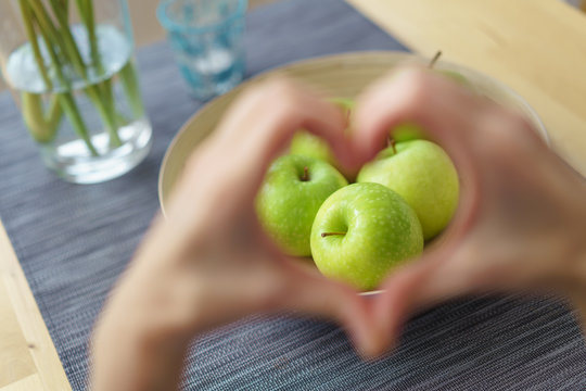 frau zeigt ein herz mit den händen mit äpfeln im fokus