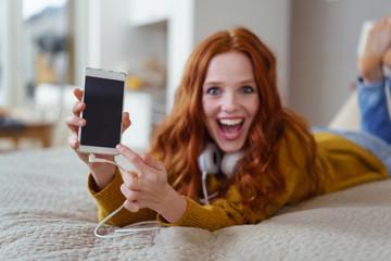 frau mit handy und kopfhörern zeigt auf den display ihres smartphones