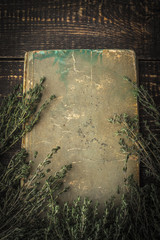 Old book with thyme on the wooden table vertical