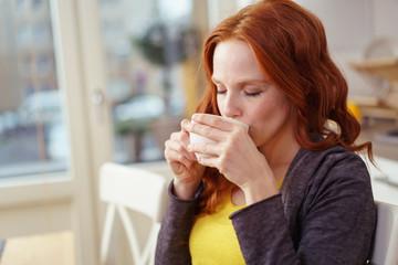 frau trinkt eine tasse tee zu hause in der küche