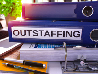 Outstaffing - Blue Ring Binder on Office Desktop with Office Supplies and Modern Laptop. Outstaffing Business Concept on Blurred Background. Outstaffing - Toned Illustration. 3D Render.