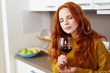 frau genießt ein glas rotwein zu hause