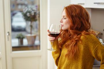 frau trinkt ein glas rotwein zu hause