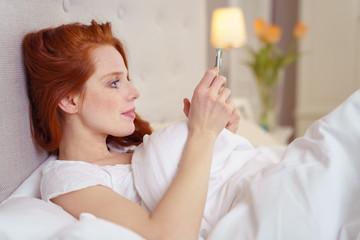 frau liegt im bett und schaut auf ihr mobiltelefon