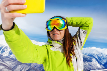 Skier woman take selfie with phone over mountains