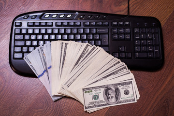 keyboard and money, a place for records, business plan, money background, hundred dollar bills front side. background of dollars, new hundred-dollar bil face, copyspace, earnings in the Internet